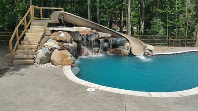 hand crafted stone waterfeature with multiple waterfalls and custom slide