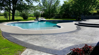 new gunite swimming pool with waterfall, tanning ledge, pebble sheen surface, custom concrete deck