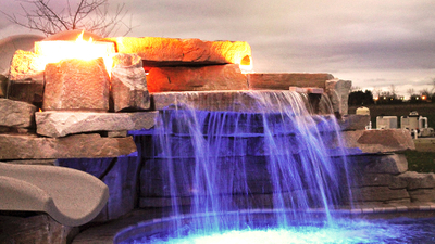 hand crafted stone waterfall with custom slide and automated fire features