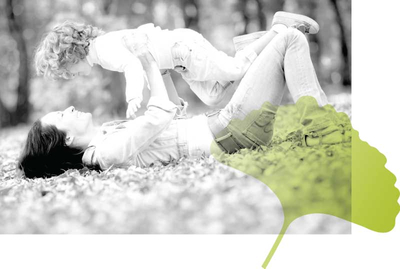 Mother Lying  Outdoors Lifting her Child Up in Play with Gingko Leaf Accent from Well Within Logo
