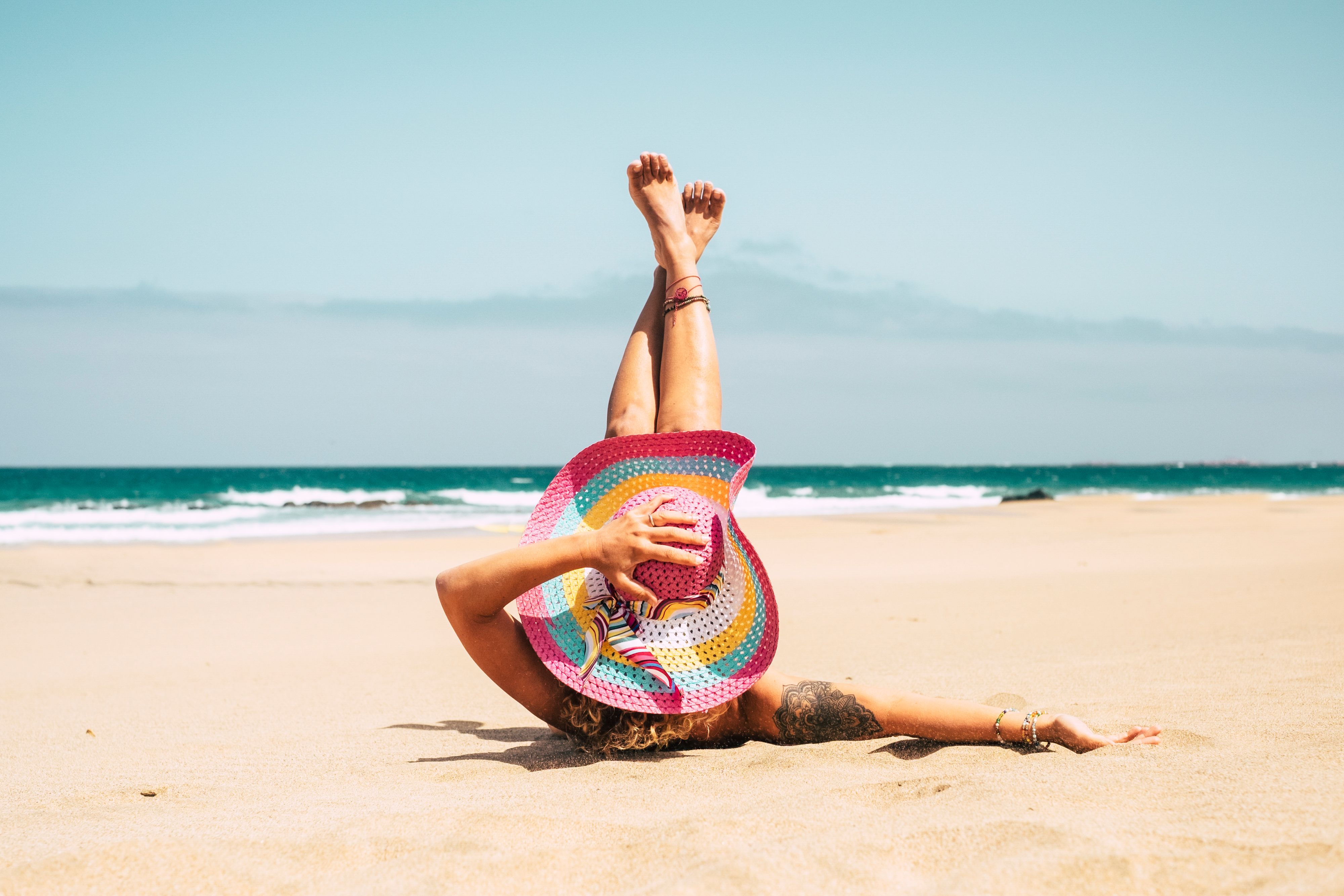 woman-with-colorful-hat-enjoy-the-beach-laying-on--CNK7TDX.jpg