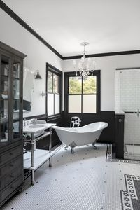 Black and white tiles and a silver-footed soaking tub