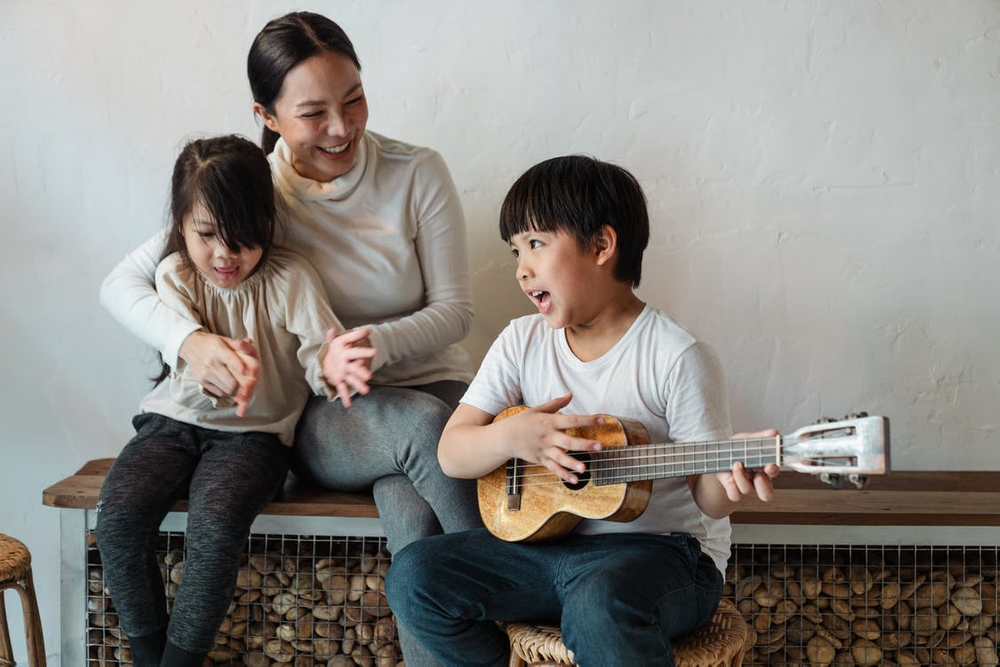 A boy playing ukulele while sitting with his mother and sister