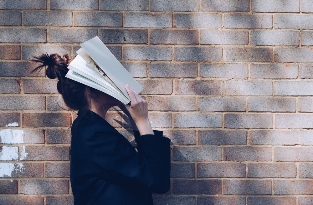 a girl with a book over her head