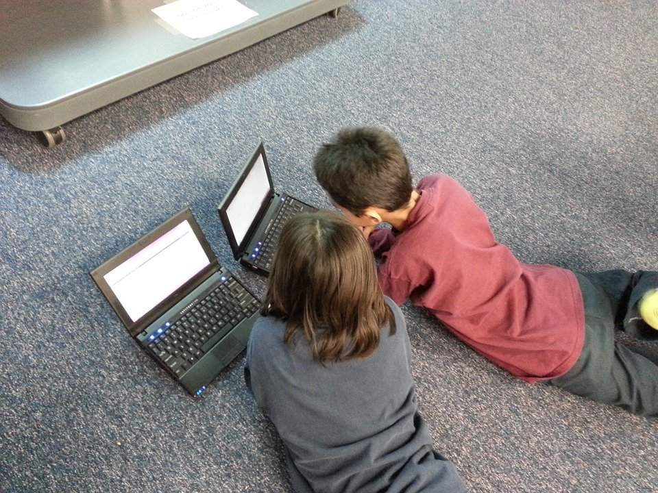 Two kids using their laptops