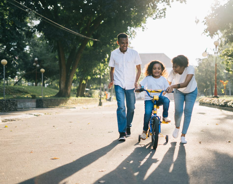 Parents teaching their child to ride a bike by instilling confidence