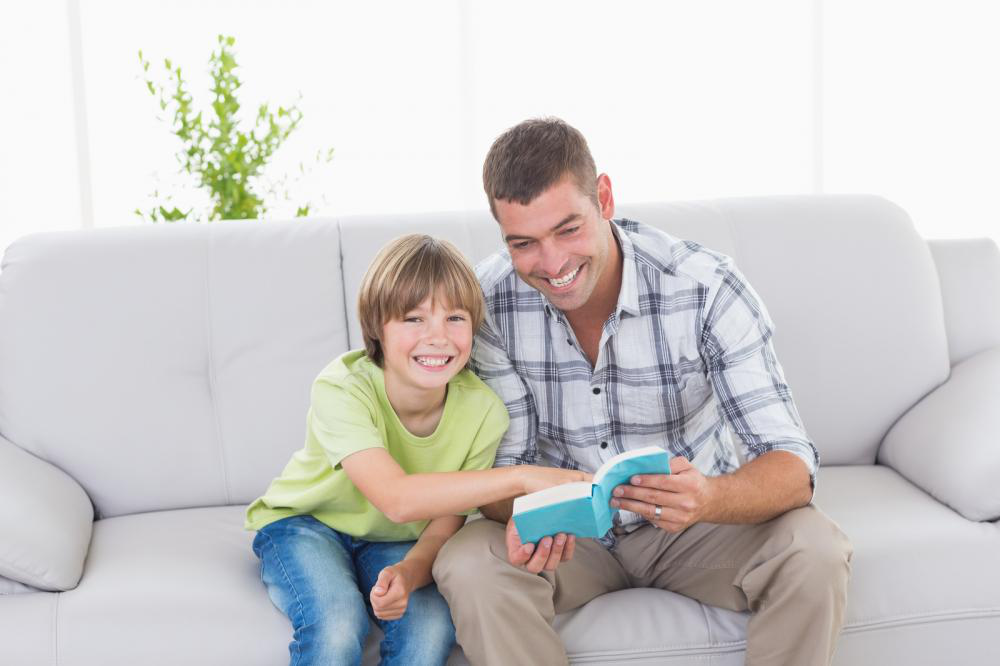 Father and son sitting on a sofa with a storybook