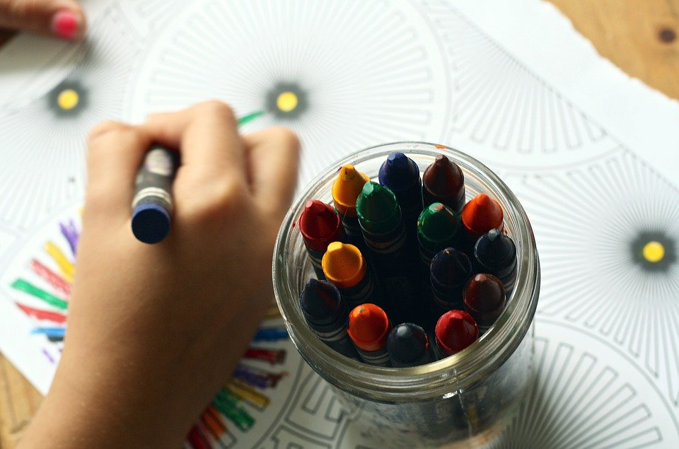 A kid coloring with crayons