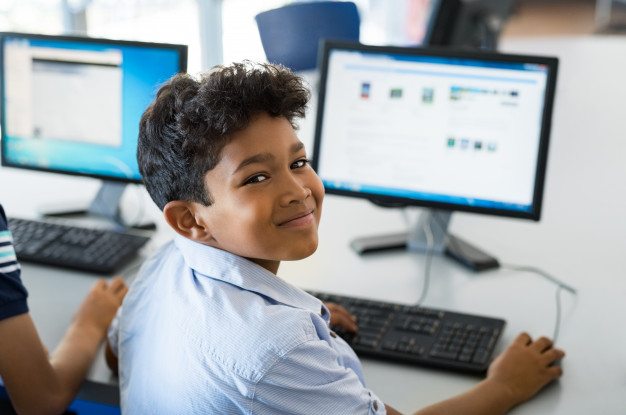 A young schoolboy smiling while learning digitally