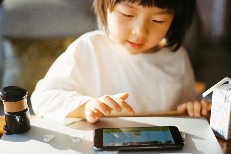 A child playing a brain-teaser game on a smartphone