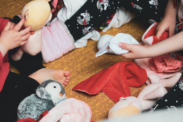 A mother sorting clothes and toys with her baby