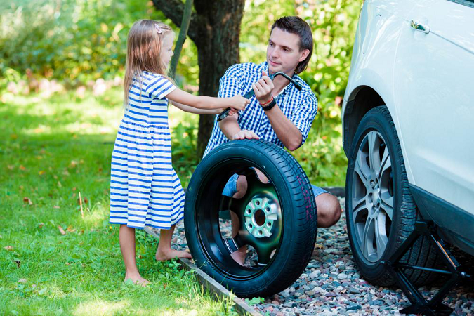 A girl helping her father with changing the tires