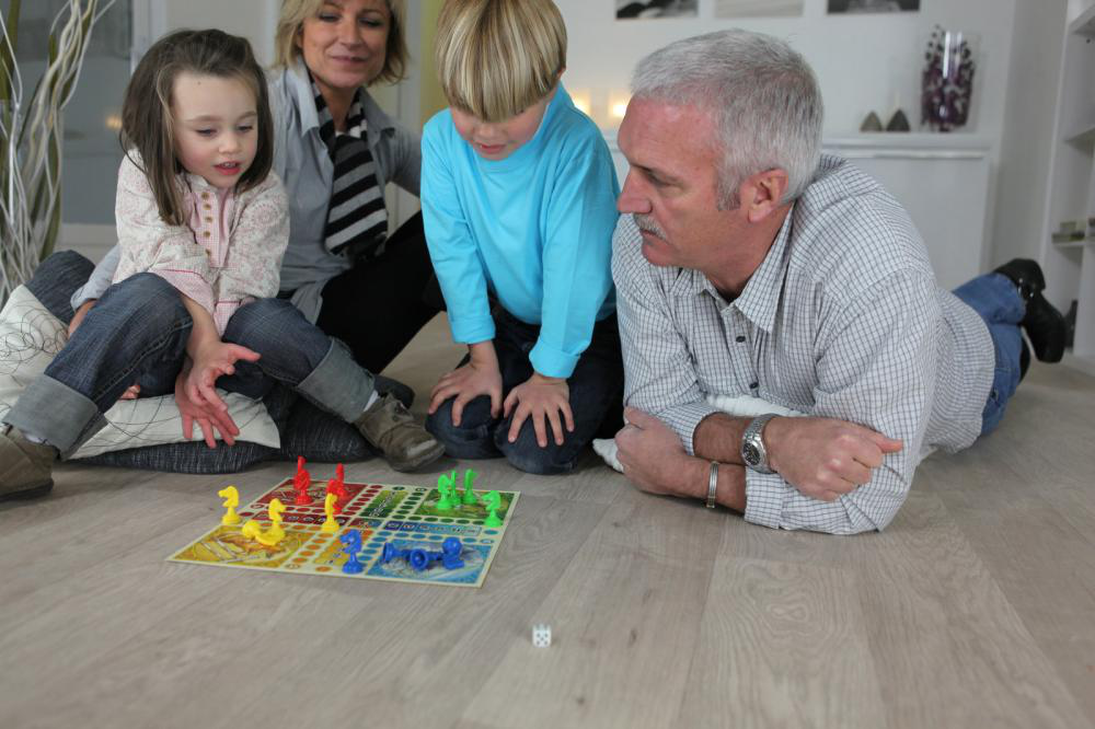Grandchildren learning to play Ludo with from their grandparents