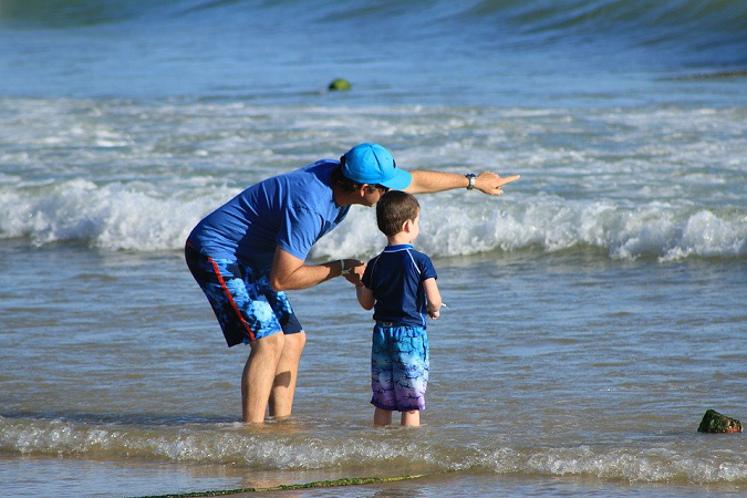 Father standing with his son on the seashore pointing at something