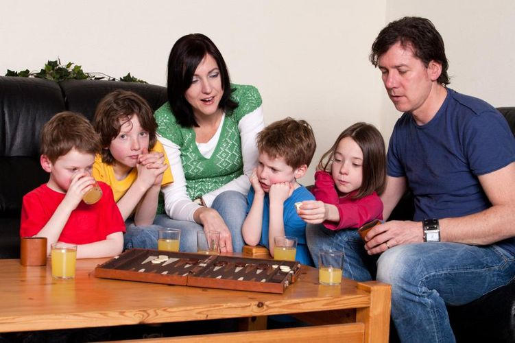 A family playing backgammon and drinking juice