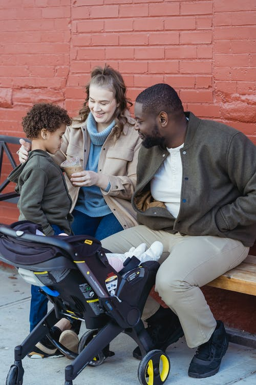A family sitting on a bench and talking