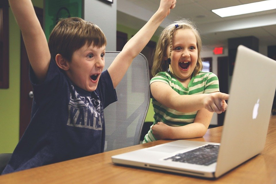 Two excited kids looking at a laptop screen