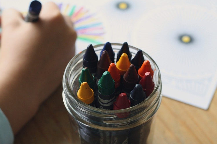 A child coloring a sheet of paper with crayons