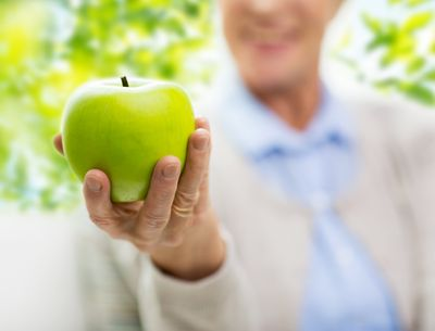 close-up-of-senior-woman-hand-holding-green-apple-PBVTQX2.jpg
