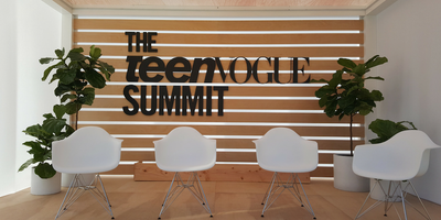 Teen Vogue Summit Panel Stage with white chairs and plants