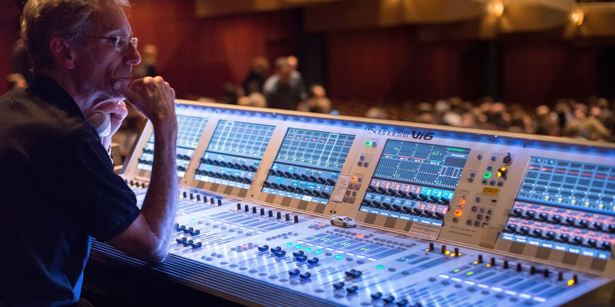 Audio engineer sitting at a Soundcraft sound board