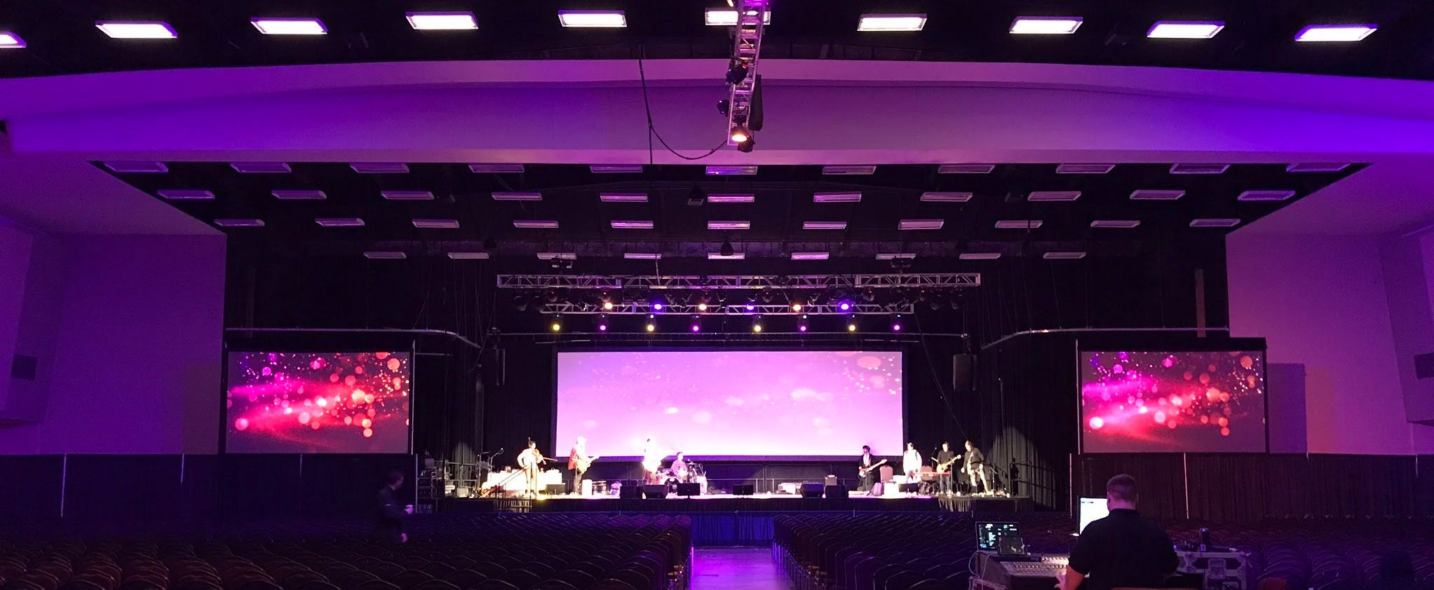 Image of Large Conference with three screen display pink, purple and blue led lighting