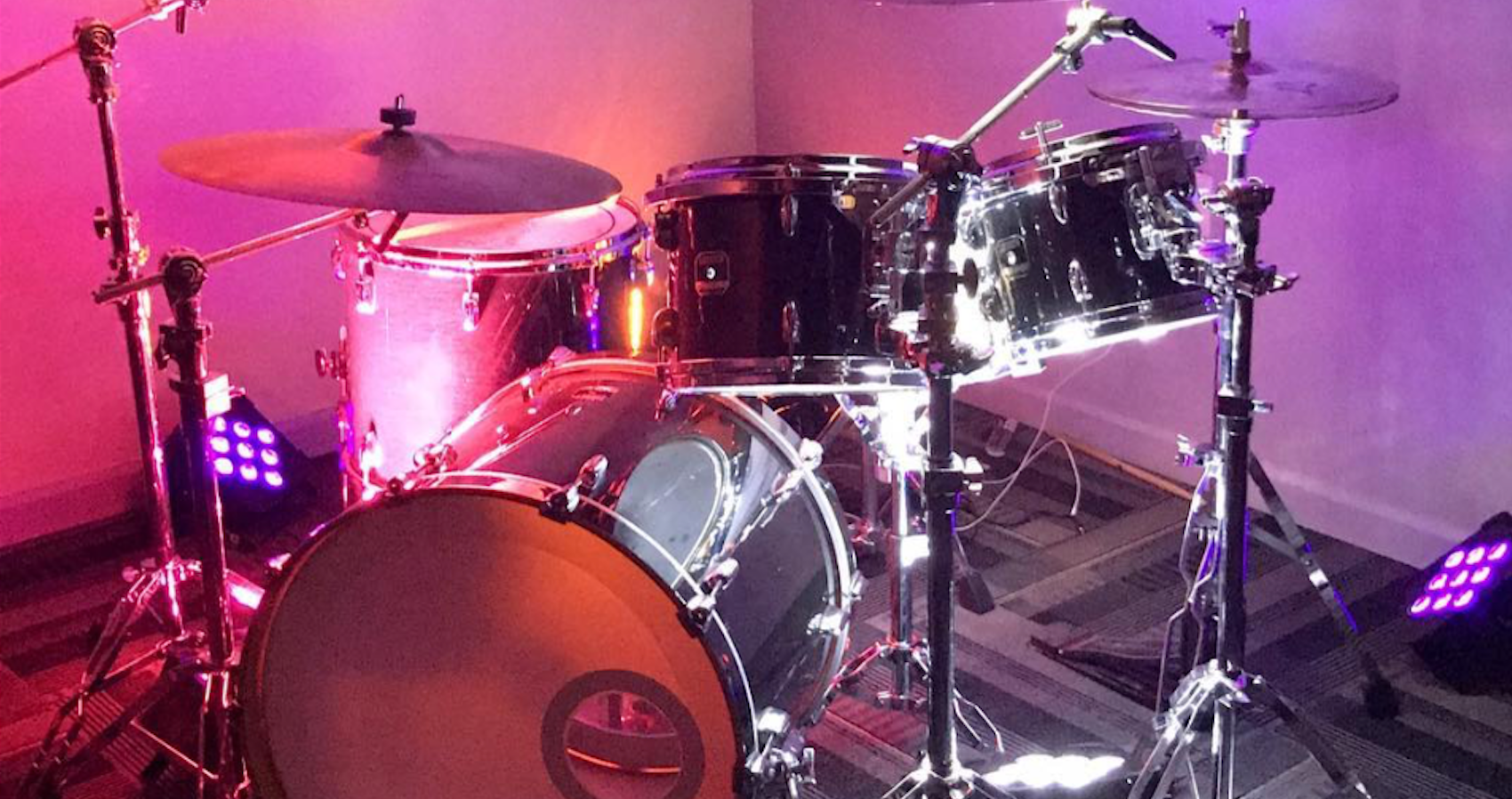 Drum kit set up in TSV Sound & Vision's shop with pink led uplighting
