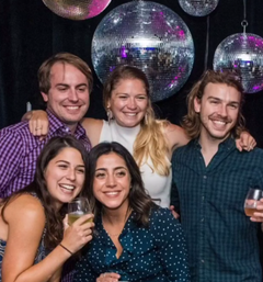 Group of people pictured at a party with disco balls in the background
