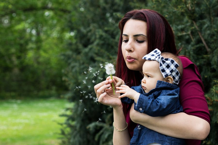 woman-holding-baby-while-blowing-dandelion-2224959.jpg
