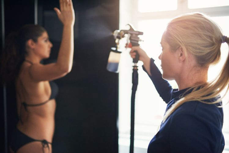 beautician-spraying-tan-on-woman-in-salon-PY8FMHQ.jpg