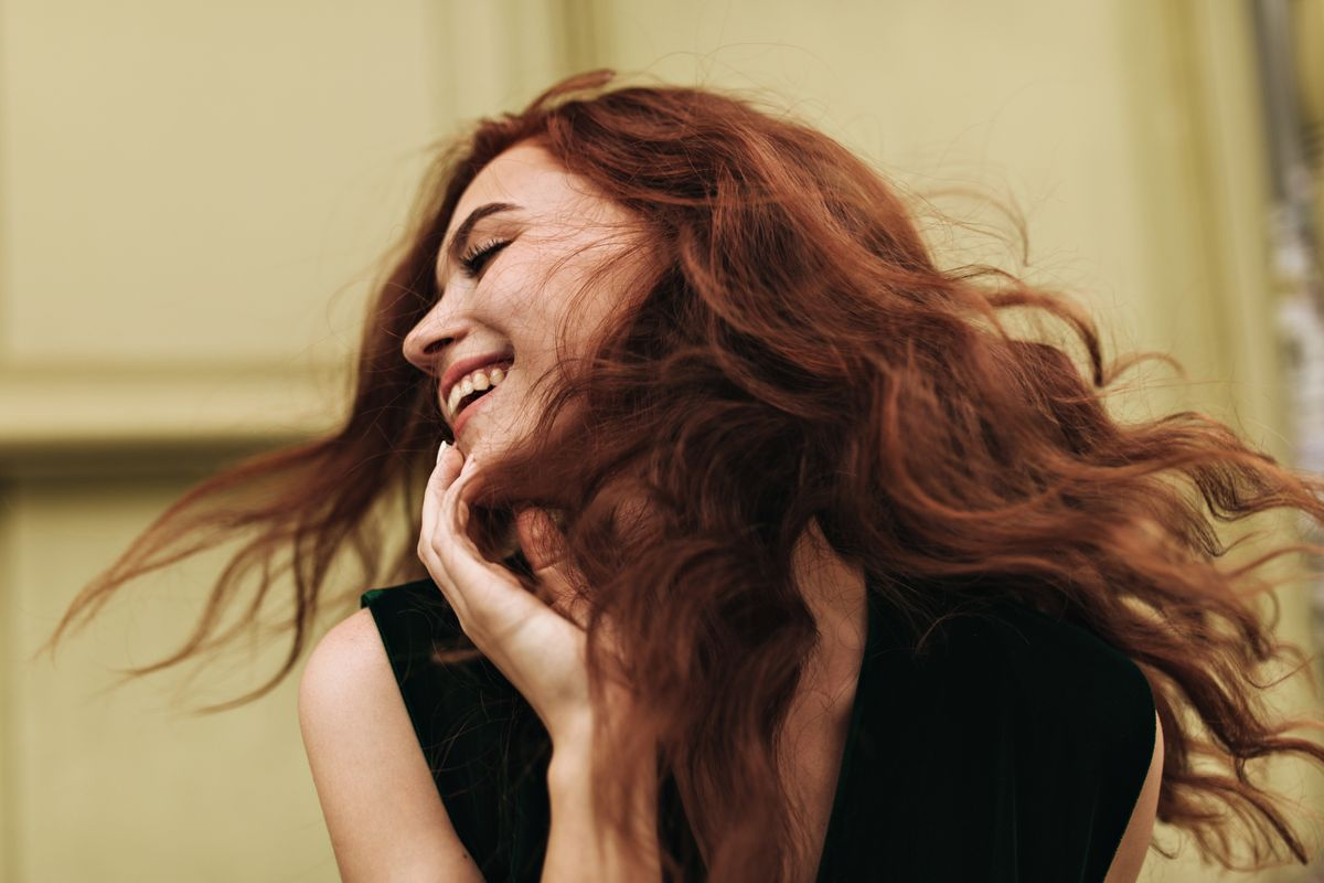 curly-woman-posing-outside-and-laughing-85LNH7K.jpg