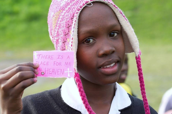 "young girl holding sign that says ""There is a place for me in heaven"""